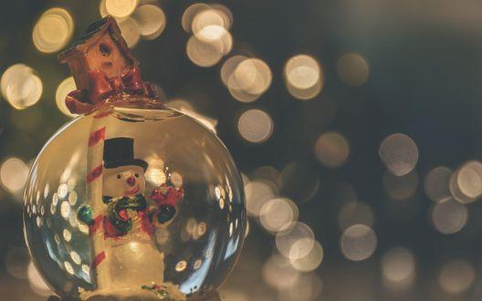 Обои Стеклянный шар со снеговиком внутри