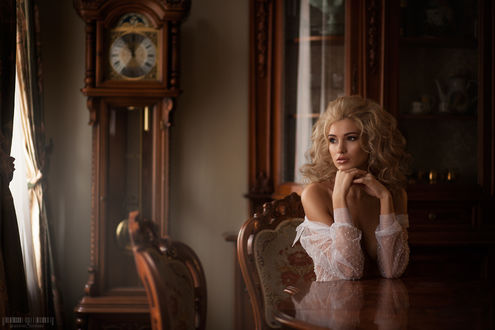 Обои Красивая блондинка - модель Анна Азхар в прозрачной одежде задумчиво сидит за столом by Anton Komar
