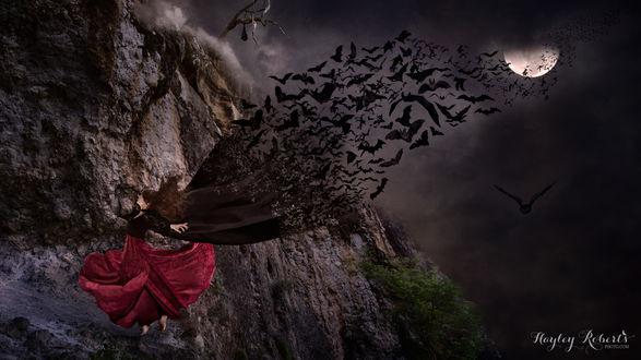 Обои Девушка рыжеволосая в красной юбке стоит на выступе скалы. Из ее накидки вылетают летучие мыши, by Hayley Roberts