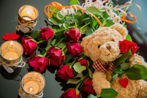 Обои Игрушечный мишка и букет красных роз рядом, горящие свечи, фотограф NamtaN NamtaN