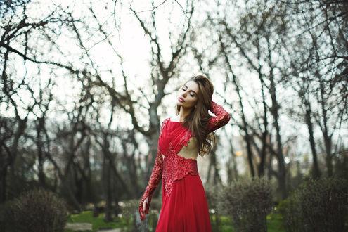 Обои Девушка красивая шатенка в красном полу ажурном платье стоит на фоне весеннего пейзажа опустив глаза и поправляя свои волосы, by Tamerlan Kagermanov