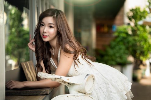 Обои Улыбающаяся азиатка в белом платье облокотилась на подоконник