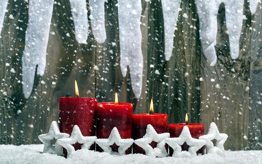Обои Красные свечи стоят по порядку, вокруг них снежинки из снега