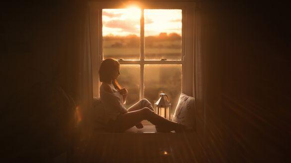 Обои Девушка сидит у окна, освещенная солнцем