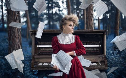 Обои Девушка в красном платье стоит на фоне природы и пианино, вокруг летают листы с нотами