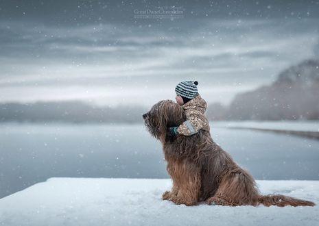 Обои Маленький мальчик стоит обняв собаку на фоне зимнего пейзажа