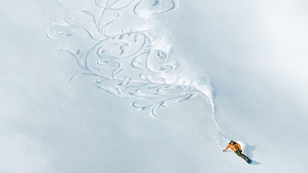Обои для рабочего стола Горнолыжник при спуске с горы, нарисовал лыжами узоры на снегу