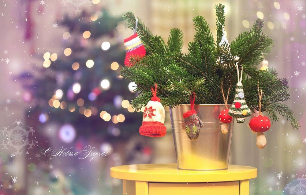 Обои для рабочего стола Вязанные игрушки висят на сосновых ветках, стоящих в ведре на тумбочке на размытом фоне, С новым годом!