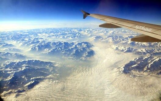 Обои Под крылом самолета раскрывается красивый пейзаж - горы под облаками, by Mafkef