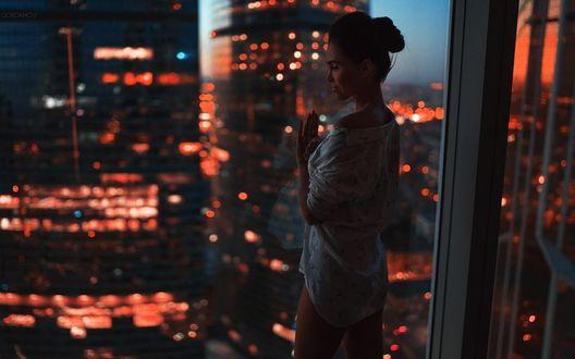 Обои Девушка стоит у окна, за которым ночной город, фотограф Иван Горохов