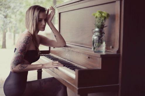Обои Грустная девушка-блондинка в нижнем белье, с татуировкой на предплечье, сидит облокотившись рукой о пианино, держа в руке сигарету, на крышке пианино стоит графин с цветами на фоне природы