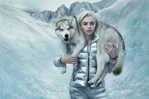 Обои Девушка блондинка держит на шее собаку хаски на фоне зимних гор, by Annie Leibovitz