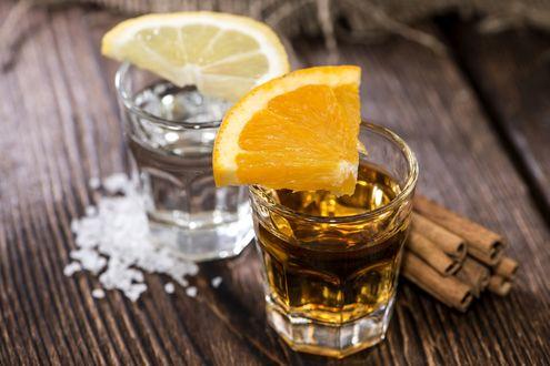 Обои Алкогольный напиток текила в прозрачных стаканах с кусочками лимона, солью и корицей