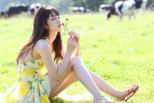 Обои Японская певица, бывшая участница группы Morning Musume, Мичишиге Саюми / Michishige Sayumi сидит на траве в поле в цветастом платье и нюхает полевые цветы