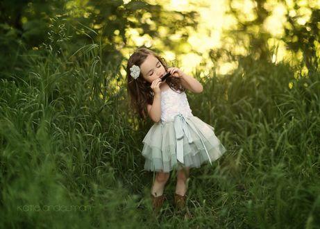 Обои Красивая маленькая девочка в белом платье с цветком в волосах стоит в траве, играя на губной гармошке, by Katie Andelman