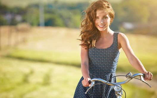 Обои Красивая девушка с рыжими волосами улыбающаяся стоит на размытом фоне летнего пейзажа держа руль велосипеда