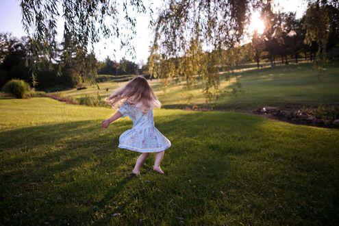 Обои Маленькая белокурая босоногая девочка кружится в танце на фоне природы