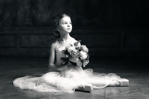 Обои Юная балерина сидит с букетом на полу в зале