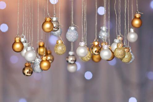 Обои Разноцветные елочные шары висят на веревках на размытом сером фоне