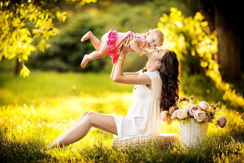 Обои Любящая мама подняла вверх на руках свою дочурку на фоне летнего пейзажа