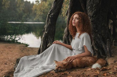 Обои Рыжеволосая девушка сидит на берегу водоема смотря вдаль, рядом с девушкой лежит лиса, которую она нежно гладит по шерстке