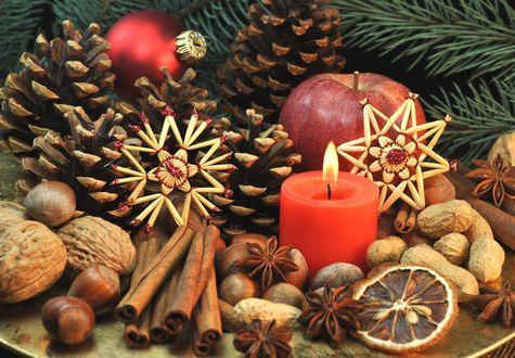 Обои На новогоднем столе праздничное угощение - яблоки, палочки корицы, грецкие орехи, звездочки аниса, лесные и земляные орешки, дольки грейпфрута все это рядом с кедровыми шишками, зажженной свечой, веткой сосны и елочной игрушкой