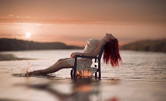 Обои Рыжеволосая девушка сидит, наслаждаясь природой, погрузив красивые ноги в ласковые волны моря и любуясь заходящим солнцем, медленно уходящем за горизонт