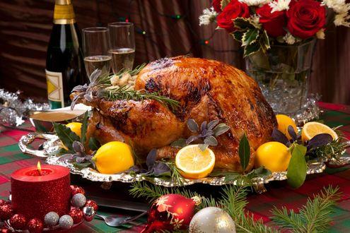 Обои Рождественская индейка, украшенная нарезанными лимонами, пахучими травами - розмарином, красным базиликом, лавровыми листьями, рядом елочные игрушки, свеча и бутылка вина Рейнхессен (Молоко любимой женщины) с фужерами