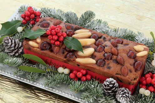 Обои Шоколадный новогодний кекс, украшенный разными орешками, по бокам яркие гроздья рябины, шишки и еловые веточки