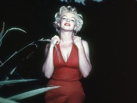 Обои Marilyn Monroe / Мерилин Монро в красном открытом платье стоит на фоне черного неба
