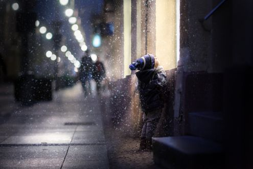 Обои Маленький мальчик стоит снежным вечером перед освещенным окном на городской улице