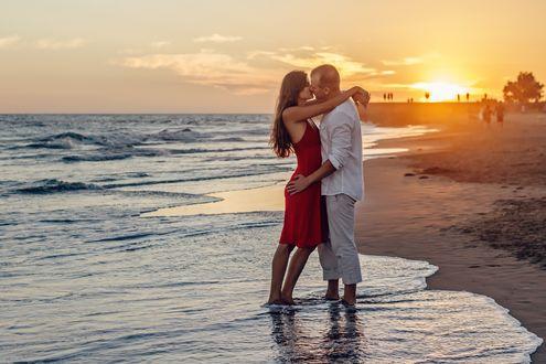 Обои Парень обнимает девушку, оба стоят на побережье