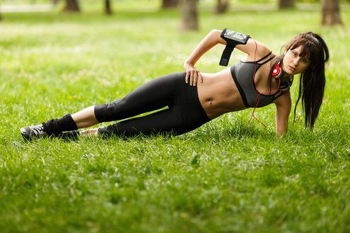 Обои Спортивная девушка с наушниками тренируется на траве в парке