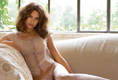 Обои Модель Ирина Шейк / Irina Sheik в ажурной кофте и чулках сидит на диване