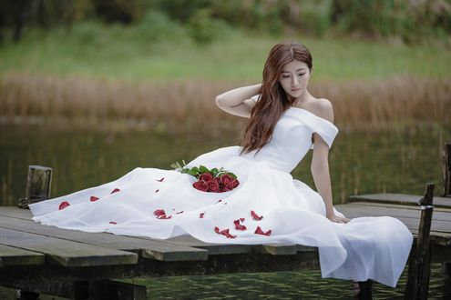 Обои Азиатка в свадебном платье с букетом сидит на деревянном мостике у пруда