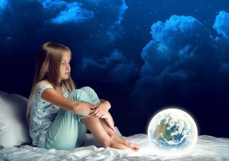 Обои Девочка сидит на постели с планетой