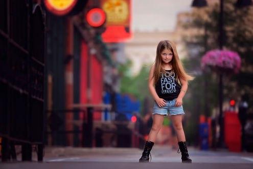 Обои Девочка, в голубых шортах, черных майке и ботинках, стоит на улице города, расставив ноги