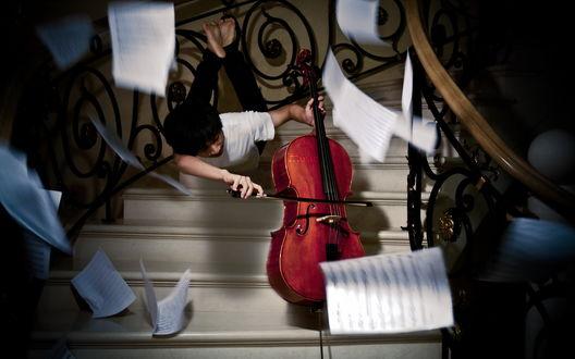 Обои Мужчина паря над лестницей играет на виолончели, Вокруг летают листы с нотами