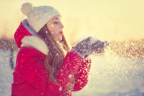 Обои Девушка в шапочке и розовой куртке держит перед собой руки со слетающим снегом