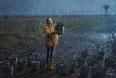 Обои Девушка с ведром в руках стоит под дождем, фотограф Roman Makhmutov