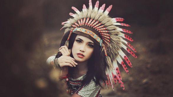 Обои Девушка в индейском головном уборе из перьев и меха, вышивкой на ленте на размытом фоне