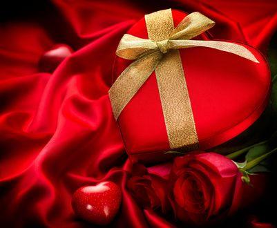 Обои Подарочная коробка в форме сердечка перевязана золотой лентой рядом с алыми розами на алом шелке