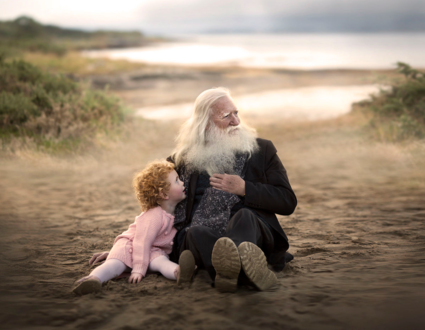 Обои Маленькая девочка с рыжими кудрявыми волосами сидит с седовласым и бородатым дедом на песчаном берегу на фоне водоема, by Elena Shumilova