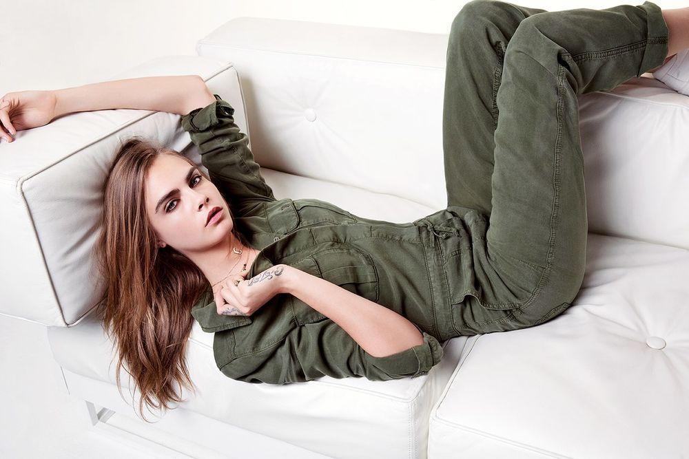 Обои для рабочего стола Модель Cara Delevingne с татуировкой на руке и пальце в комбинезоне цвета хаки лежит на диване