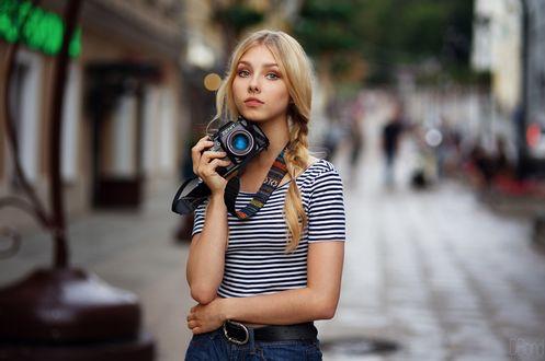 Обои Модель Алиса Тарасенко / Alice Tarasenko с косичками в полосатом топе и шортах с фотоаппаратом в руке задумавшись стоит на размытом фоне города. Фотограф Ден Евдокимов / DBond