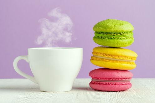 Обои Цветные макаруны рядом с белой чашкой с напитком