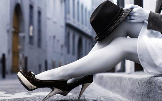 Обои Ножки сидящей на городской улице девушки и шляпка на коленке