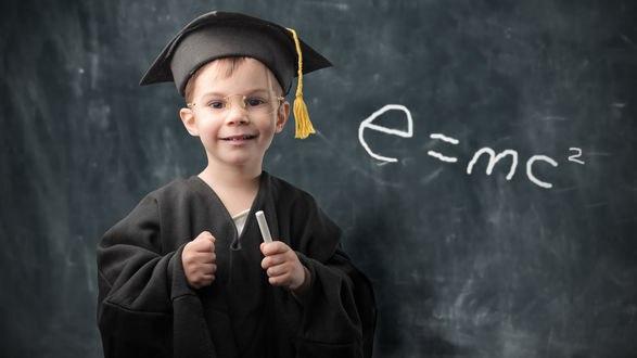 Обои Юный физик с мелом в руке на фоне школьной доски