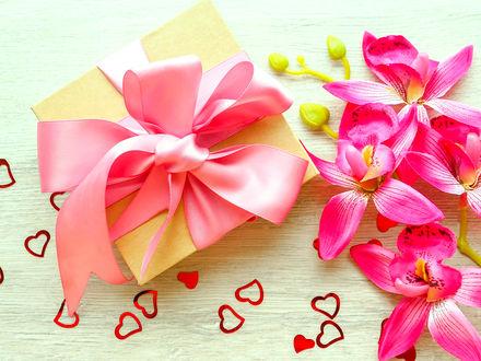 Обои Коробка с подарком перевязана розовой лентой, рядом сердечки и ветка искусственной орхидеи