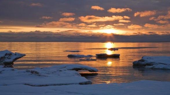 Обои Заснеженный берег зимнего озера на фоне заката над облачным горизонтом